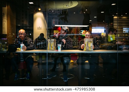 NEW YORK, USA - Apr 30, 2016: Group of men in a cafe having breakfast. Manhattan street scene. The Americans on the streets of New York City