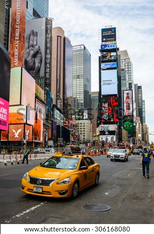 NEW YORK, USA - AUGUST 7, 2015: A yellow cab drives past Times Square. - stock photo