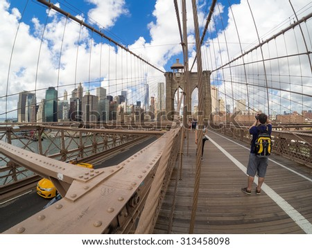 NEW YORK,USA- AUGUST 20,2015 : Tourists at the Brooklyn Bridge in New York with a view of the Manhattan skyline - stock photo