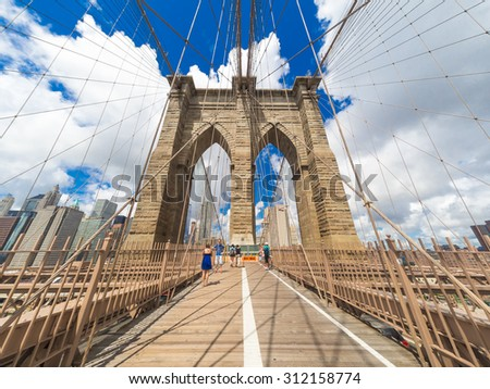 NEW YORK,USA- AUGUST 20,2015 : Tourists at the Brooklyn Bridge on a beautiful summer day - stock photo