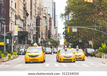 NEW YORK, USA - AUGUST 24, 2014: Typical yellow taxi in Manhattan street. Yellow cabs are a famous icon of New York city. - stock photo