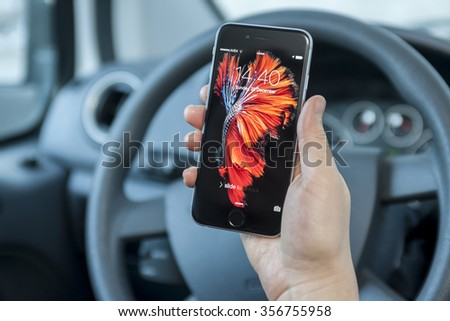 New York, USA - December 21, 2015:  Female  using her space grey color iPhone 6S smart phone in the car. - stock photo