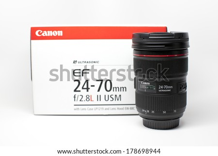 New York, USA - July 2, 2013: Canon EF 24-70mm f/2.8L II USM isolated on a white surface and with Canon lens box at the background.  - stock photo