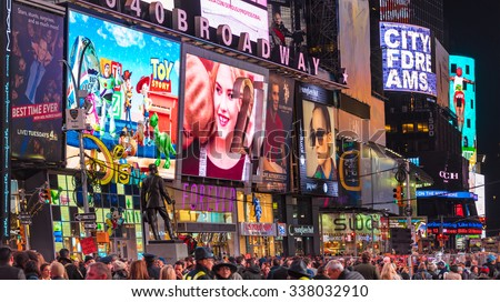 NEW YORK,USA-JULY 5,2015:New York Times Square night scenes featuring the crowd and neon ads. The tourist landmark is visited by about 50 million tourists every year  - stock photo