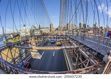 NEW YORK, USA JULY 9, 2010: people at Brooklyn bridge in New York City. It's a bridge in New York City and is one of the oldest suspension bridges in the United States. - stock photo