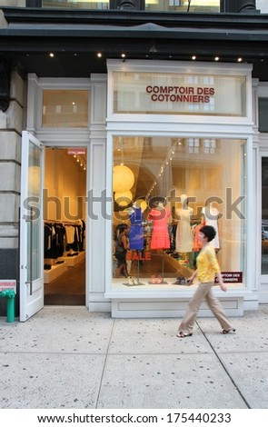 NEW YORK, USA - JULY 3, 2013: Shopper walks by Comptoir Des Cotonniers store in 5th Avenue, New York. 5th Avenue is ranked the most expensive retail area (per square foot) in the world.