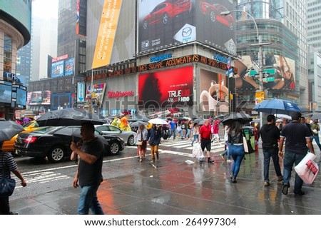 NEW YORK, USA - JUNE 10, 2013: People walk in rain in Times Square, New York City. Times Square has over 39 million annual visitors. It is an important landmark of Midtown Manhattan.