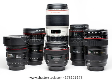 New York, USA - March 20, 2013: Set of Canon EF lenses containing a 15mm fish-eye, a 16-35mm, a 50mm, a 100mm Macro lens, a 24-105mm kit lens and a 70-200mm tele. - stock photo