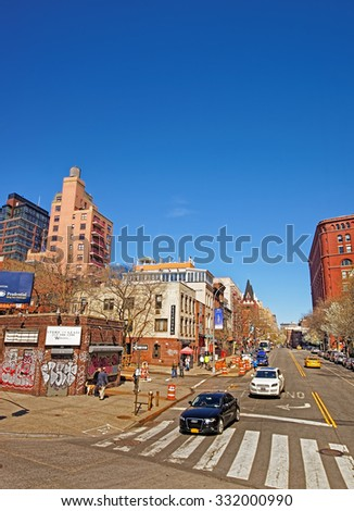 NEW YORK, USA - MAY 07, 2015: View of sunny New York City street with brown brick buildings and speeding cars. Manhattan, New York, USA                - stock photo