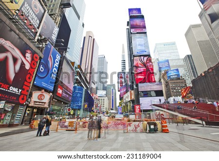 NEW YORK, USA - NOVEMBER 13th, 2014: People walking through New York's famous Times Square area with colorful signage. - stock photo