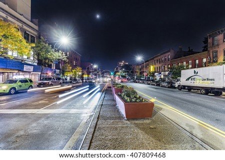 NEW YORK, USA - OCT 20, 2015: night view in Brooklyn Park slope of main street with headlights of cars in New York. The 4th avenue is a main street in Brooklyn with lots of old victorian brick houses. - stock photo