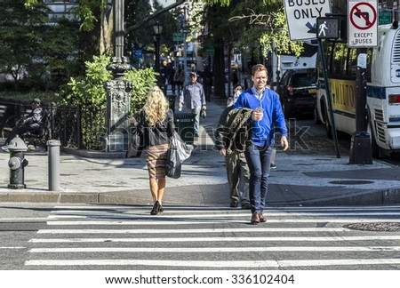 NEW YORK, USA - OCT 21 2015: people crossing a street at a pedestrian crossing in New York. New York State averages nearly 300 pedestrian fatalities annually. - stock photo