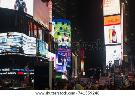 NEW YORK, USA - 9 of October 2017: Broadway Times Square at night, with a lot of displays, neon lights and other advertisement, cars on road and people