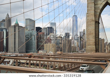 NEW YORK, USA - SEP 08, 2014: Skyscrapers in Manhattan, view through the wire ropes of the Brooklyn Bridge