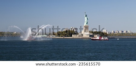 NEW YORK, USA, SEPT 27: The New York City Fire Department Boat practices maneuvers  in the Hudson River of New York City and Statue of Liberty on September 27, 2014 - stock photo