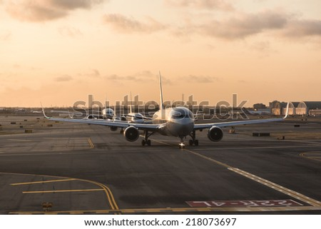 NEW YORK, USA - SEPTEMBER 10, 2014: American Airlines airplanes waiting to take off from JFK Airport. New York city skyline on background.