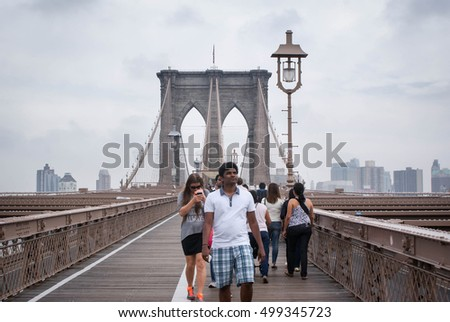 New York, USA - September 22, 2014: Tourists stroll the famous Brooklyn bridge in New York, USA