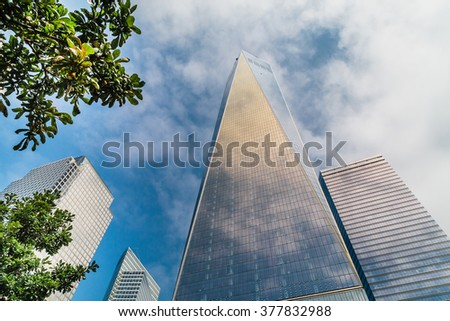 New York, USA - 5 September 2014:  View looking up at the One World Trade Center and other skyscrapers set against a slightly cloudy, blue sky
