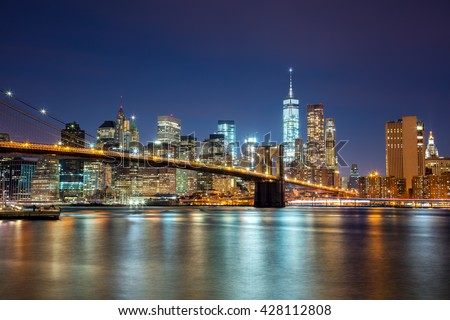 New York -  view of Manhattan Skyline with skyscrapers  and famous Brooklyn Bridge by night and city illumination, USA - stock photo
