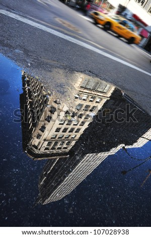 New York Yellow cab pass over a reflection of the Empire State Building in Manhattan, New York. - stock photo