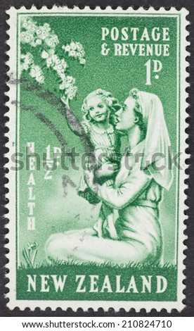 NEW ZEALAND - CIRCA 1949: A Cancelled postage stamp from New Zealand illustrating a nurse holding a child, issued in 1949. - stock photo