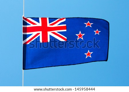 New Zealand flag in the wind against the sky - stock photo
