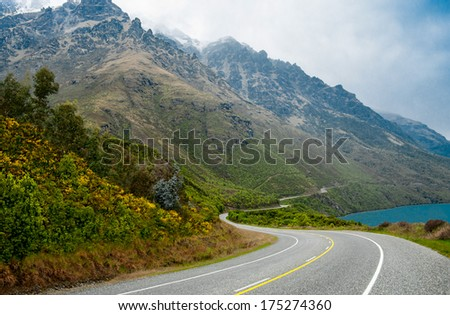New Zealand Scenic Road:  A two lane road passes beside a lake and winds along the base of a misty mountain south of Queenstown on New Zealand's South Island.  - stock photo