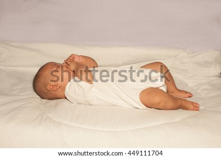 Newborn Asian baby girl lying and happiness on a bed.