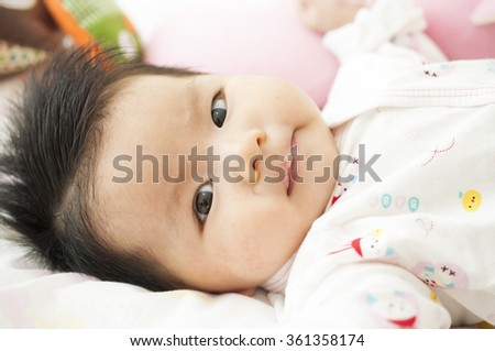 Newborn asian baby girl  play and smile on bed - stock photo