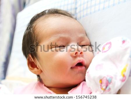 Newborn Asian baby girl sleeping - stock photo
