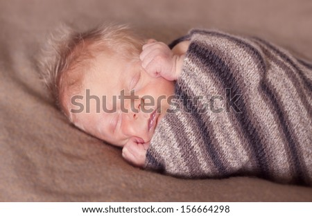 Newborn baby all swaddled in a blanket and sleeping.