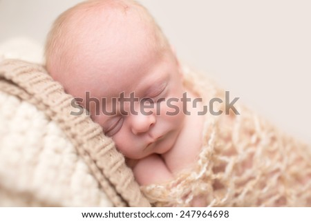 Newborn Baby Asleep, sleeping and taking a nap on a textured blanket posed and curled up - stock photo