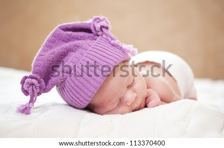 newborn baby (at the age of 14 days) sleeps in a knitted  hat - stock photo