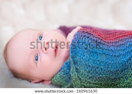 Newborn baby awake and relaxed wrapped in a colourful blanket