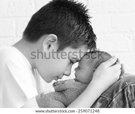 Newborn baby being held tenderly by big brother - stock photo