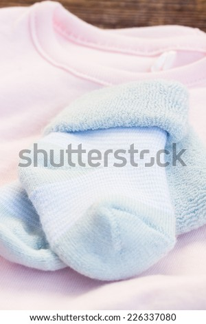 newborn baby blue socks on pink  clothes close up