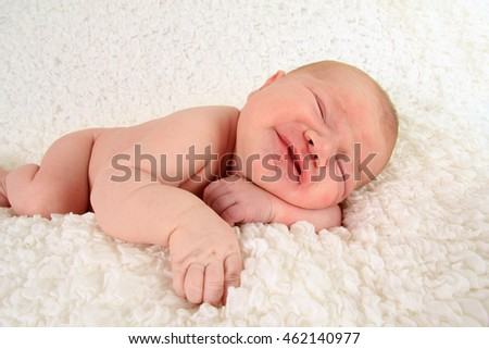 Newborn baby boy frowning with colic.