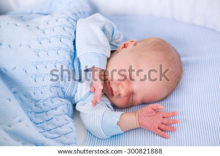 Newborn baby boy in bed. New born child sleeping under a blue knitted blanket. Children sleep. Bedding for kids. Infant napping in bed. Healthy little kid shortly after birth. Cable knit textile. - stock photo