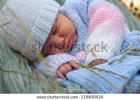 newborn baby boy in knitted jacket asleep at the garden - stock photo