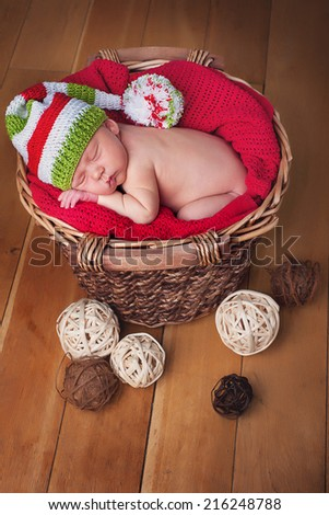Newborn baby boy portrait, in blanket, basket, stripe hat, red blanket - stock photo