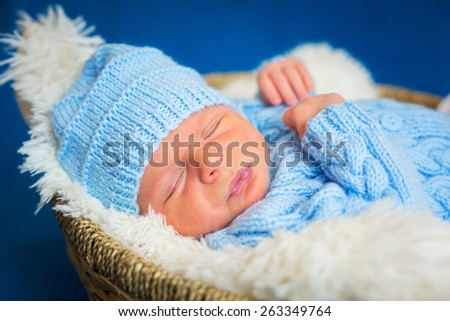 Newborn baby boy portrait in blue knitted hat - stock photo
