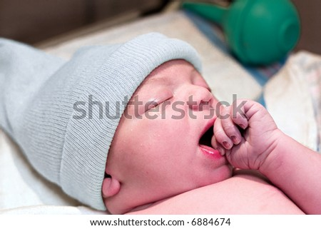 Newborn baby boy resting in hospital with hand in mouth - stock photo