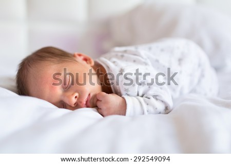 Newborn baby boy sleeping in bed - stock photo