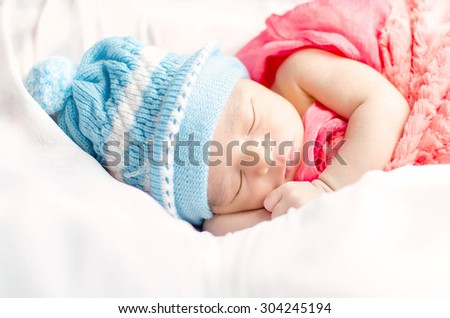 Newborn baby boy sleeping in busket waering blue hat and red blanket isolated in white background