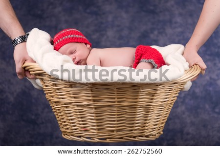 Newborn baby boy sleeping on a white blanket in a wicker basket. The basket is being held by his parents. Infant is wearing a red knit cap and diaper cover. Soft focus with a shallow depth of field. - stock photo
