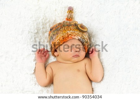 Newborn Baby boy sleeping while wearing a hat on his head. - stock photo