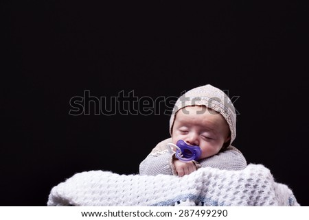 Newborn baby boy sleeping with a pacifier - stock photo