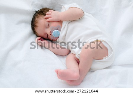 Newborn baby boy sleeping with pacifier - stock photo