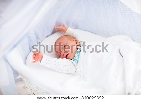 Newborn baby boy waking up on a sunny morning in white bed. New born child sleeping and stretching in moses basket under knitted blanket. Children sleep. Bedding for kids. Infant napping in bed.