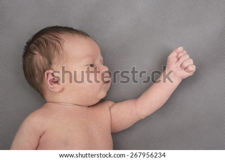 Newborn baby boy with clenched fist - stock photo
